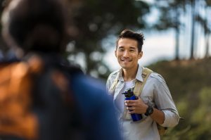Happy hiker with bottle and backpack in forest